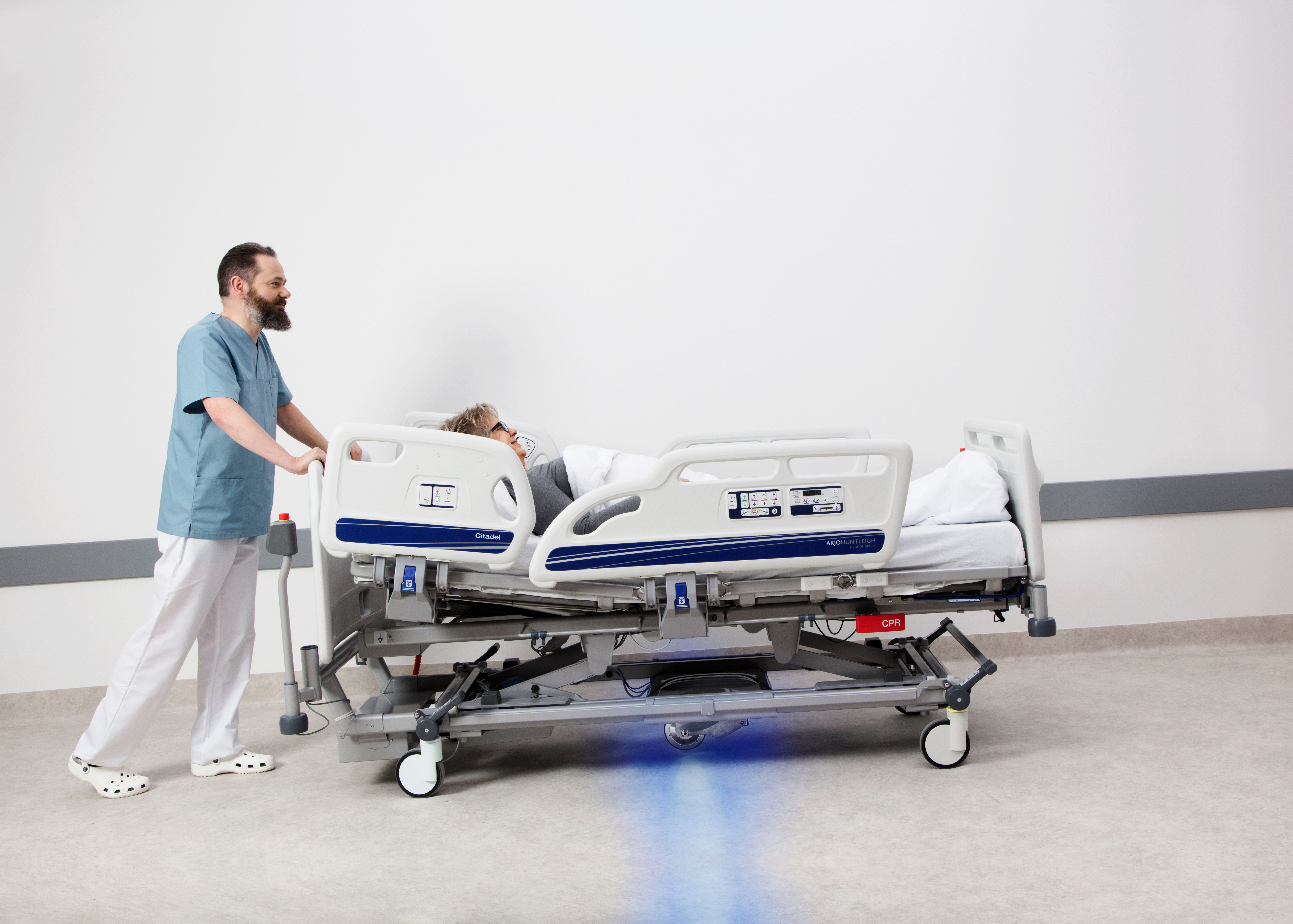 What technologies are used to aid caregivers in transporting patients on hospital beds?